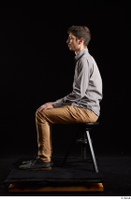 Falco White  1 black shoes brown trousers dressed grey shirt sitting whole body 0001.jpg