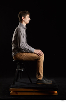 Falco White  1 black shoes brown trousers dressed grey shirt sitting whole body 0005.jpg