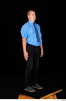 Paul Mc Caul black belt black trousers blue shirt blue shoes business dressed standing tie whole body 0008.jpg