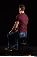 Tomas Salek  1 blue jeans dressed grey shoes red t shirt sitting whole body 0002.jpg