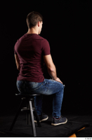 Tomas Salek  1 blue jeans dressed grey shoes red t shirt sitting whole body 0004.jpg