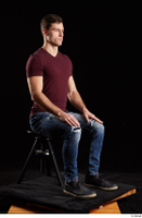 Tomas Salek  1 blue jeans dressed grey shoes red t shirt sitting whole body 0006.jpg