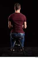 Tomas Salek  1 blue jeans dressed grey shoes red t shirt sitting whole body 0011.jpg