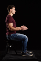 Tomas Salek  1 blue jeans dressed grey shoes red t shirt sitting whole body 0013.jpg