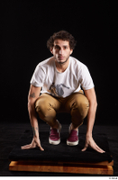 Pablo  1 brown trousers dressed kneeling red sneakers white t shirt whole body 0001.jpg