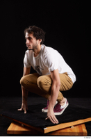Pablo  1 brown trousers dressed kneeling red sneakers white t shirt whole body 0002.jpg