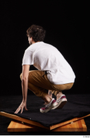 Pablo  1 brown trousers dressed kneeling red sneakers white t shirt whole body 0004.jpg