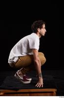 Pablo  1 brown trousers dressed kneeling red sneakers white t shirt whole body 0007.jpg