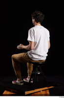 Pablo  1 brown trousers dressed red sneakers sitting white t shirt whole body 0010.jpg