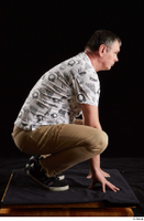 Spencer  1 black sneakers brown trousers dressed kneeling white printed t shirt whole body 0007.jpg