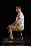 Spencer  1 black sneakers brown trousers dressed sitting white printed t shirt whole body 0001.jpg