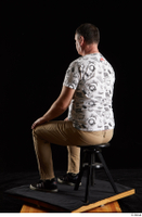 Spencer  1 black sneakers brown trousers dressed sitting white printed t shirt whole body 0002.jpg
