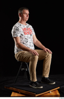 Spencer  1 black sneakers brown trousers dressed sitting white printed t shirt whole body 0006.jpg