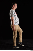 Spencer  1 black sneakers brown trousers dressed side view walking white printed t shirt whole body 0003.jpg