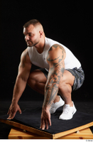 Grigory  1 camo shorts dressed kneeling sports white sneakers white tank top whole body 0002.jpg