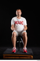 Louis  2 dressed grey shorts red sneakers sitting sports white t shirt whole body 0015.jpg