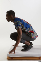 Kavan  1 black sneakers dressed grey pants kneeling traditional african t shirt whole body 0003.jpg