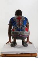 Kavan  1 black sneakers dressed grey pants kneeling traditional african t shirt whole body 0005.jpg
