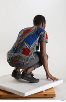 Kavan  1 black sneakers dressed grey pants kneeling traditional african t shirt whole body 0006.jpg