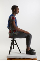 Kavan  1 black sneakers dressed grey pants sitting traditional african t shirt whole body 0005.jpg
