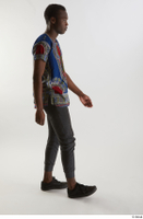 Kavan  1 black sneakers dressed grey pants side view traditional african t shirt walking whole body 0001.jpg