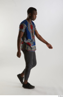 Kavan  1 black sneakers dressed grey pants side view traditional african t shirt walking whole body 0002.jpg